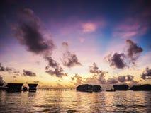 Schattenbild von Wasserlandhaushäuschen bei Sonnenaufgang oder Sonnenuntergang Lizenzfreies Stockfoto
