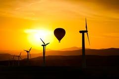 Schattenbild von Windkraftanlagen und eine Heißluft steigt f-Berge und den Sonnenuntergang im Ballon auf Lizenzfreie Stockbilder
