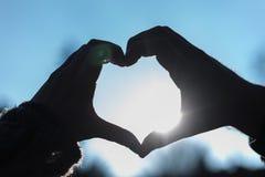 Schattenbild von zwei Händen, die ein Herz machen, formen in Richtung zum Himmel Lizenzfreie Stockbilder