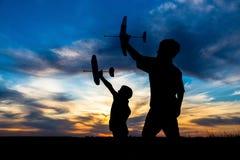 Schattenbild von zwei Jungen mit seinen Flugzeugen gegen Sonnenuntergang Lizenzfreies Stockfoto