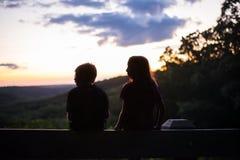 Schattenbild von zwei Kindern, die Sonnenuntergang aufpassen stockfotografie
