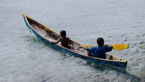 Schattenbild von zwei lokalen Jungen in einem Boot auf Arborek-Insel in Raja Ampat, West-Papua, Indonesien, nahe dem berühmten Ma Stockfoto