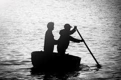 Schattenbild von zwei Männern, die in gesponnenem Bambuskorbboot rudern stockfotos