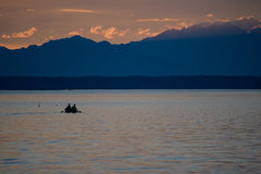 Schattenbild von zwei Männern, die in einem Boot mit Bergen im Abstand rudern Lizenzfreies Stockfoto
