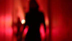 Schattenbild von zwei sexy Frauen in den hohen Absätzen, die in einen undeutlichen, roten Korridor tanzen stock video