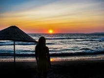 Schattenbildaufenthalt der jungen Frau auf dem Strand durch das Meer stockfotografie