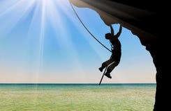 Schattenbildbergsteiger, der einen Berg klettert Lizenzfreie Stockbilder