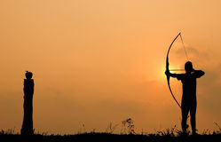 Schattenbildbogenschießen schießt einen Bogen auf einen Apfel auf Bauholz Lizenzfreies Stockfoto
