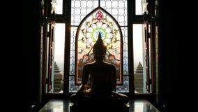 Schattenbildbuddha-Statue hat Blume und Sonne Muster beflecktes gla Stockfoto
