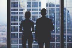 Schattenbilder der hinteren Ansicht von zwei Teilhabern, die durchdacht aus einem Bürofenster in der Situation des Konkurses hera stockfotografie