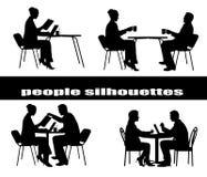 Schattenbilder der Leute an einem Tisch Stockbilder