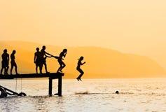 Schattenbilder des Kindspringens Stockfoto