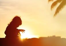 Schattenbilder des kleinen Mädchens spielen am Sonnenuntergangstrand Stockbild