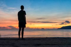Schattenbilder des Mannes auf Strand bei einem bunten Sonnenaufgang mit ?berraschendem Himmel ?ber Ozean lizenzfreie stockfotografie