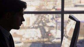 Schattenbilder des Mannes, der am Computer auf Fenster am Nachmittag arbeitet 4K stock video