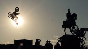 Schattenbilder des Monuments, der Gruppe von Personen, die darunterliegend stehen und der springenden Radfahrer stock video footage