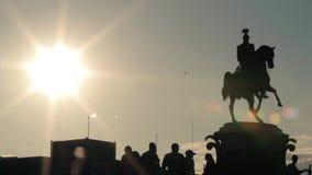 Schattenbilder des Monuments, der Gruppe von Personen, die darunterliegend stehen und der springenden Radfahrer stock video