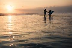 Schattenbilder des Paarhändchenhaltens und der Brandungsbretter bei Sonnenuntergang auf Küstenlinie Stockfotografie