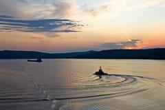 Schattenbilder des Pilot- und Frachtschiffs am Sonnenuntergang Stockbild