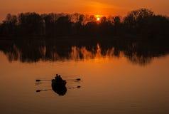 Schattenbilder des romantischen Paarsegelns in einem Boot gegen den Hintergrund des orange Sonnenuntergangs lizenzfreie stockbilder