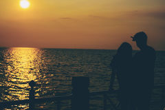 Schattenbilder des Umarmens von Paaren gegen das Meer bei Sonnenuntergang Stockfoto