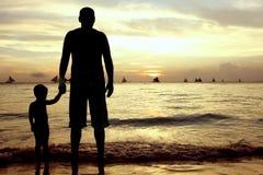 Schattenbilder des Vaters und des Sohns auf Seehintergrund lizenzfreie stockfotos