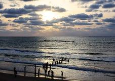 Schattenbilder einer Gruppe ipeople gegen das Abendmeer und -himmel Stockbilder
