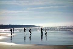 Schattenbilder Leute, die auf dem Strand spielen Lizenzfreie Stockbilder