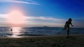 Schattenbilder Leute spielen Badminton auf dem Strand bei Sonnenuntergang stock footage