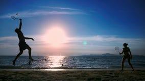 Schattenbilder Leute spielen Badminton auf dem Strand bei Sonnenuntergang stock video footage
