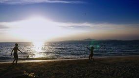 Schattenbilder Leute spielen Badminton auf dem Strand bei Sonnenuntergang stock video