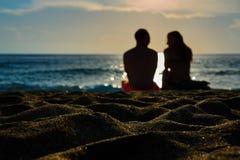 Schattenbilder Paare, des Mannes und der Frau sitzen auf einem sandigen Strand und betrachten den Sonnenuntergang auf dem Meer au lizenzfreie stockfotografie