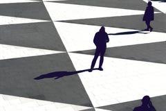 Schattenbilder und Schatten von den Leuten, die auf einem offenen Quadrat stehen Stockfotografie