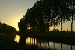 Schattenbilder von Bäumen und von buntem Abendhimmel nach dem Sonnenuntergang, der im Wasser sich reflektiert Stockfotografie
