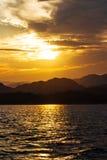Schattenbilder von Bergen eines Sonnenuntergangs über dem Meer Lizenzfreie Stockfotos