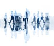 Schattenbilder von den gehenden Geschäftsleuten und von Stadt-Hintergrund lizenzfreies stockbild