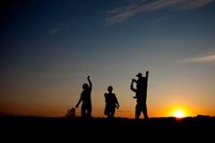 Schattenbilder von den glücklichen Eltern, die gute Zeit mit ihrem kleinen haben lizenzfreie stockfotos