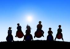 Schattenbilder von den Kindern, die auf Bällen spielen Stockfotos