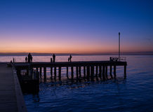 Schattenbilder von den Leuten, die auf einem Pier bei Sonnenuntergang stehen Lizenzfreie Stockbilder