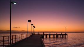 Schattenbilder von den Leuten, die auf einen Pier bei Sonnenuntergang gehen Stockfotografie