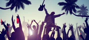 Schattenbilder von den Leuten, die ein Konzert auf dem Strand genießen Lizenzfreie Stockfotos