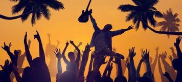 Schattenbilder von den Leuten, die ein Konzert auf dem Strand genießen Lizenzfreies Stockfoto