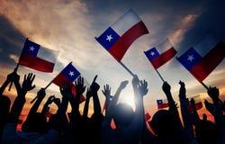 Schattenbilder von den Leuten, die Flagge von Chile halten stockfoto