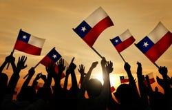 Schattenbilder von den Leuten, die Flagge von Chile halten Lizenzfreie Stockbilder