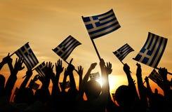 Schattenbilder von den Leuten, die Flagge von Griechenland halten Lizenzfreie Stockfotos