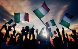 Schattenbilder von den Leuten, die Flagge von Italien halten Lizenzfreie Stockfotografie