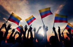 Schattenbilder von den Leuten, die Flagge von Kolumbien halten Stockbild