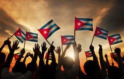 Schattenbilder von den Leuten, die Flagge von Kuba halten Stockbild