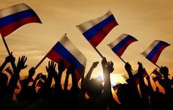 Schattenbilder von den Leuten, die Flagge von Russland halten Stockfotografie