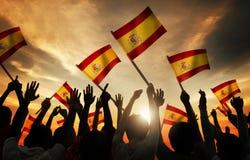 Schattenbilder von den Leuten, die Flagge von Spanien halten Stockbild